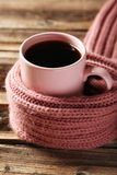 Kopp kaffe med den varma halsduken på den bruna träbakgrunden Royaltyfria Bilder