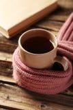 Kopp kaffe med den varma halsduken på träbakgrund Royaltyfri Foto