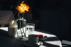 Kopp kaffe med en bukett av den gula pingstliljan royaltyfri fotografi