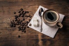 Kopp kaffe med en sked på en servett och kaffebönor Fotografering för Bildbyråer