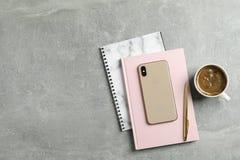 Kopp kaffe med förskriftsböcker, telefonen och pennan på grå bakgrund royaltyfri foto