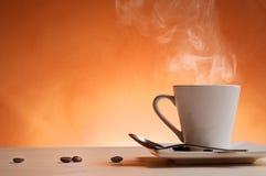 Kopp kaffe med främre sikt för orange bakgrund Fotografering för Bildbyråer