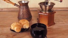 Kopp kaffe med giffel Nytt bryggat kaffe med bullar i köket En gammal kaffekvarn och en turk stock video