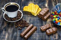 Kopp kaffe med godisar arkivfoto