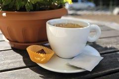 Kopp kaffe med godisen på tabellen Royaltyfria Bilder