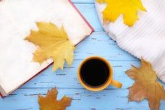 Kopp kaffe med höstsidor och den gamla boken på blå bakgrund fotografering för bildbyråer