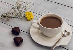 Kopp kaffe med hjärta formade choklader och blommor Royaltyfri Foto