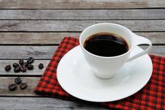 Kopp kaffe med kaffebönor och den röda näsduken på träbakgrund royaltyfria foton