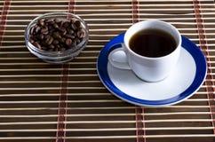 Kopp kaffe med kaffekorn på ett tefat Royaltyfri Bild