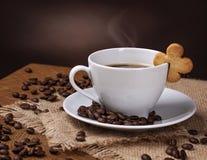 Kopp kaffe med kakan Arkivbild
