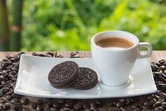 Kopp kaffe med kakan på tabellen Arkivfoton
