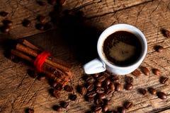 Kopp kaffe med kanelbruna near kaffebönor Arkivbilder