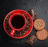 Kopp kaffe med kex och choklad på en svart bakgrund Royaltyfria Bilder
