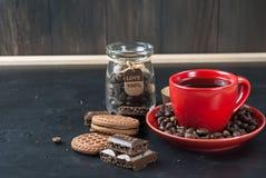 Kopp kaffe med kex och choklad på en svart bakgrund Arkivbild