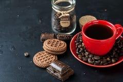 Kopp kaffe med kex och choklad på en svart bakgrund Royaltyfri Fotografi