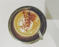 Kopp kaffe med kräm på en platta arkivbilder