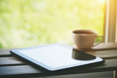 Kopp kaffe med minnestavladatoren royaltyfria bilder