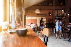 Kopp kaffe med minnestavlan på tabellen i kafé royaltyfri foto