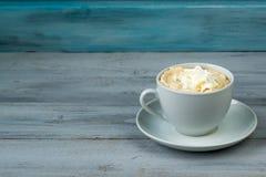 Kopp kaffe med piskad kräm på träbakgrund Arkivbild