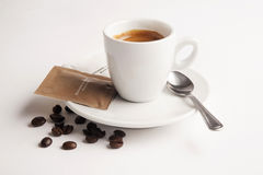 Kopp kaffe med sked-, socker- och kaffebönor Arkivbild