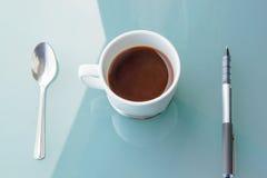 kopp kaffe med skeden och penna på tabellen Fotografering för Bildbyråer