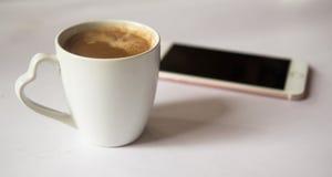 Kopp kaffe med smartphonen på vit bakgrund royaltyfri bild