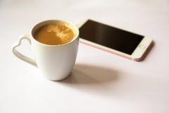 Kopp kaffe med smartphonen på vit bakgrund arkivbilder
