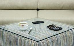 Kopp kaffe, mobiltelefon och räknemaskin på den glass tabellen Arkivfoto