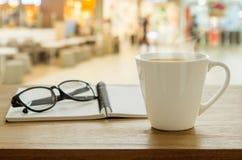Kopp kaffe, monokel och bok på trätabellen i coffee shop royaltyfri fotografi