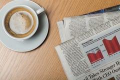 Kopp kaffe och affärstidningar Royaltyfri Bild