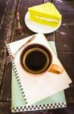 Kopp kaffe och anmärkningspapper på den wood texturbakgrundsvinten Royaltyfri Fotografi