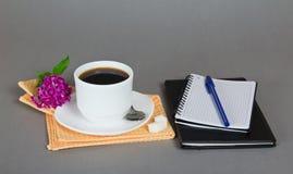 Kopp kaffe och anteckningsbok royaltyfri foto