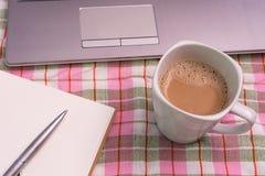 Kopp kaffe och bärbar dator på torkduken Royaltyfria Bilder