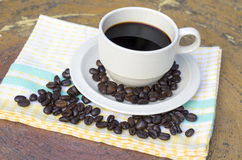Kopp kaffe och bönor på träbakgrund Fotografering för Bildbyråer