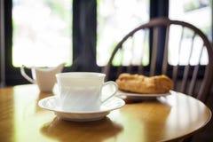 Kopp kaffe och bageri på tabellen royaltyfria bilder