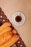 Kopp kaffe och bagett på trätabellen royaltyfri fotografi