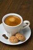 Kopp kaffe och biscotti på en trätabell arkivfoto