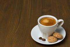 Kopp kaffe och biscotti på en trätabell royaltyfri fotografi