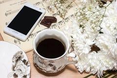 Kopp kaffe och blomma Arkivbilder