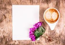 Kopp kaffe och blommor Tomt ark av papper och koppen kaffe på tabellen arkivbild