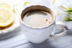 Kopp kaffe- och citronskivor på trätabellen Royaltyfri Fotografi
