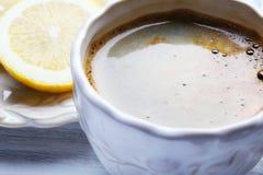 Kopp kaffe- och citronskivor på trätabellen, slut upp Royaltyfri Foto