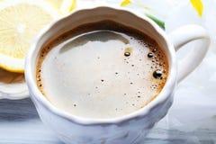 Kopp kaffe- och citronskivor på trätabellen, slut upp royaltyfri fotografi