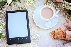 Kopp kaffe och eBookavläsaren på en tabell Fotografering för Bildbyråer