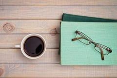 kopp kaffe och en bunt av böcker och exponeringsglas royaltyfri foto