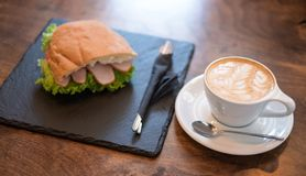 Kopp kaffe och en smörgås Arkivfoto