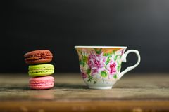 Kopp kaffe- och fransmanmacaron på den gamla trätabellen med svart bakgrund royaltyfri bild
