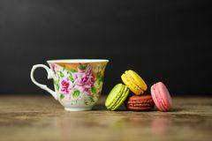 Kopp kaffe- och fransmanmacaron på den gamla trätabellen med svart bakgrund arkivfoton