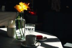 Kopp kaffe och gula påskliljor arkivbild
