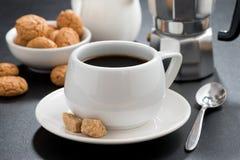 Kopp kaffe- och italienarekakabiscotti på svart bakgrund arkivbild